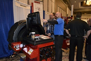 Nate Nosek, a district sales manager for Hennessy Industries Inc., demonstrates the bells and whistles on a Coats tire balancer for Point S dealer Brad Hiatt from Heber City, Utah, during the trade show.