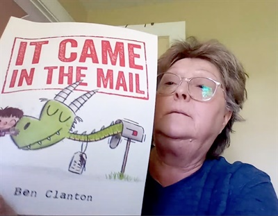 "Deb Jacobs, a bus driver for Dean Transportation, serving Bay Arenac Independent School District in Bay City, Mich., reads ""It Came in the Mail"" as part of the story time series. Screenshot courtesy Dean Transportation"