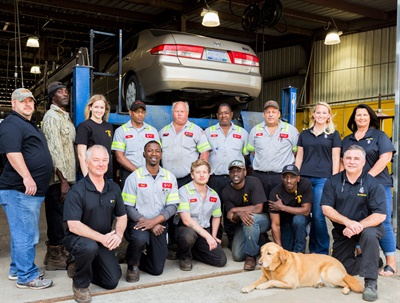 """""""Finding techs has been a challenge,"""" says Joe Bostick III, kneeling at right, next to his niece's dog, Whiskey. Also kneeling, left to right, are Robert Bostick, Verdell Floyd, Lance Harris, Kaelin Devore and Maxwell Cleveland. Standing, left to right, are Michael Thomas, Henry Gardner, Rachael Grimm, Eric Isham, Tom Summerlin, Travis Gant, Mark Padgett, Meagan Bostick and Karen Cook. Courtesy of Dr. Tire Inc."""