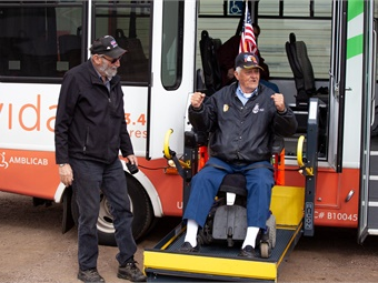 A driver for the Connection helps a disabled passenger off a vehicle.