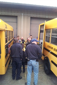 Firefighters and paramedics from three area departments in Illinois are shown how to manually operate a school bus wheelchair lift during emergency training at Durham School Services' Beach Park facility.