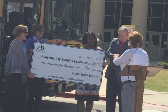School bus contractor Durham gave a bus and a $2,500 check to Huntsville (Ala.) City Schools for its Summer Feeding program.