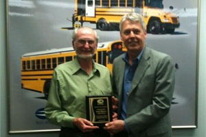 Sague Bus Service driver and trainer Earl Rineer (left) receives a plaque recognizing his dedication to public service and transporting students from Blue Bird President and CEO Phil Horlock.
