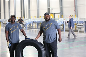 Plant employees Travis Chambliss, left, and Jason Wallace, pose with the first truck tire built in Continental's Clinton, Miss., plant.