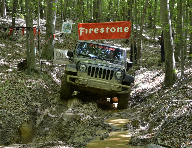 A Jeep equipped with new Firestone Destination M/T2 tires navigates a creek bed during the product's launch event in Orange, Va.