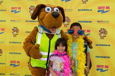 Students can pose for a photo with Safety Dog, the safety mascot for First Student, at the company's Safety Dog Bus Tour stops. Shown here are students posing with Safety Dog during the 2017 tour.