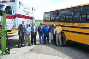 Pictured are officials from Gallipolis City School District, Gallia County Commissioners and the county's EMS division. School district technicians are maintaining the county's EMS vehicles under a new partnership.