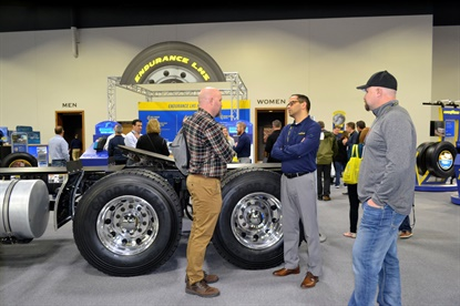 Clint Burgardt, left, and Kelly Burgardt, right, from Dakota Truck and Farm Service and Harry's Tire Service in Minot, N.D., talk to Goodyear's Mahesh Kavaturu about truck tire products during the Goodyear trade show.