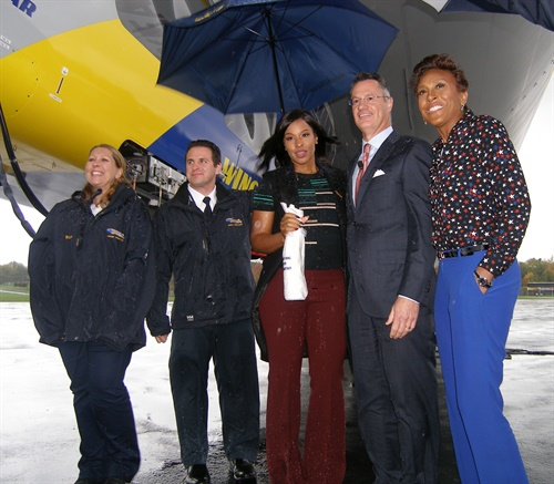 Savannah James (center), businesswoman and philanthropist, christened Goodyear's Wingfoot Two blimp on Oct. 21. The Akron, Ohio, native is pictured with (from right): Wingfoot One's christener and Good Morning America anchor Robin Roberts, and Goodyear Chairman, CEO and President Richard Kramer. At far left are blimp pilots James Kosmos and Kristen Arambula. The event was held at Goodyear's airship operations hangar near Akron, Ohio.