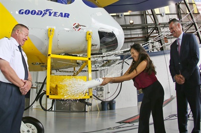 (from left) Chief Pilot Jerry Hissem, Shaesta Waiz (center) and Goodyear CEO Rich Kramer celebrate the ceremonial christening of Wingfoot Three on August 30.