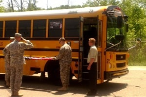 Grand Ledge Public Schools held a ceremony for two alumni who are fallen soldiers, unveiling decals that honored them on two school buses. American flags were hung in front of the decals until members of the U.S. Army took them down and folded them.