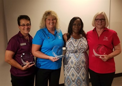 Three Gwinnett County (Ga.) Public Schools safety trainers were honored for administering CPR to bus driver Felina Canon, shown third from left. Photo courtesy Gwinnett County Public Schools
