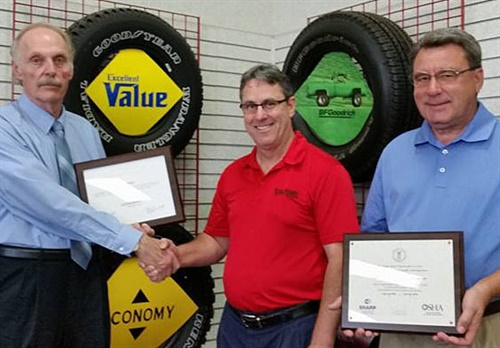 (from left): Eldon Diedrichs, project manager of the OSHA consultation program, congratulates Chuck Holman, manager of the T.O. Haas Tire store at 640 West O Street, and Randy Haas, T.O. owner and safety director of T.O. Haas Tire, for workplace safety achievement.