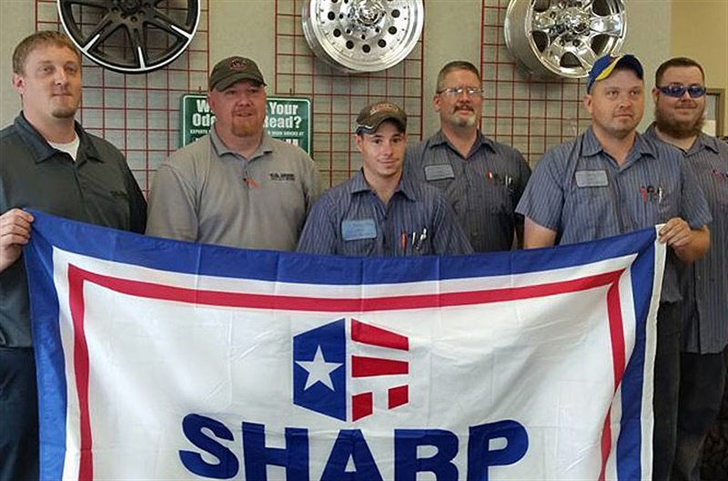 Employees of T.O. Haas Tire at the 8300 Dawson Creek Bay store display a SHARP banner earned for workplace safety. Pictured from left are Eric Schueth, Lee Davison, Kurtis Kirkindall, Jason Pounds, Kevin Bennett, and Tyler Klein.