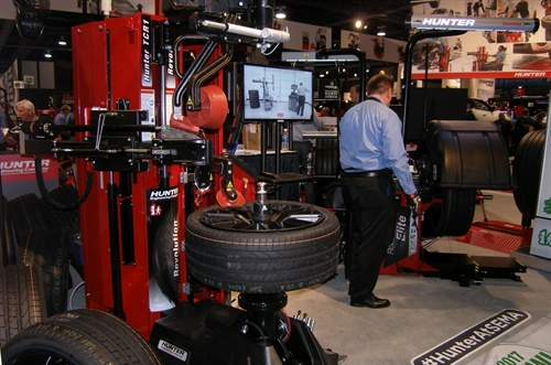 "Mike Berry ""walks away"" to balance a tire while the latest Hunter Revolution breaks the bead on a tire in a demonstration showing the autonomous capabilities of the new tire changer."