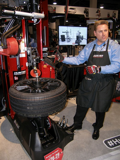 Mike Berry, a field representative for Hunter, demonstrates the time-saving features of  the new Revolution tire changer with WalkAway capability.