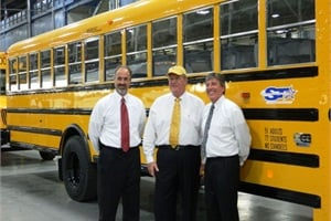 Greg Hutchison, plant manager, Denis Gallagher, Student Transportation Inc. founder and CEO, and John McKinney, president of Navistar Global Bus and IC Bus, celebrate the completion of IC Bus' 100,000th school bus at the Tulsa, Okla., plant.