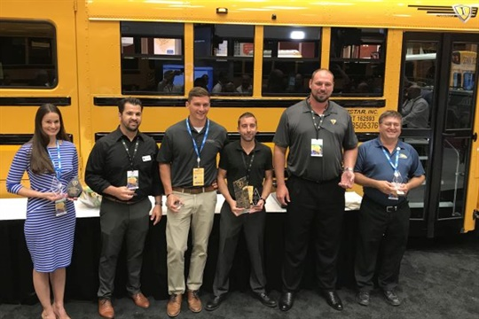 Joel Landry (middle right) of Western Canada Bus was named grand champion of the 2018 IC Bus Walk-Around Competition. Ashley Hailston (left) of Cumberland International received the People's Choice Award.