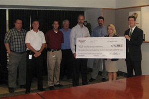Kerry Rowland (second from right) of the Public Service Company of Oklahoma presents a check for more than $142,000 to IC Bus Tulsa Plant Manager Greg Hutchison (fourth from right).