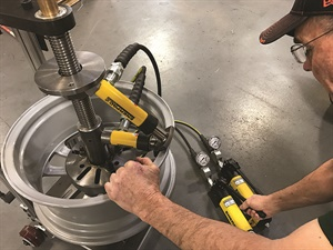 The dual-axis method is the foundation of the NewArc patent, says Neubauer (pictured straightening a Ford wheel). Note that the two hydraulic rams are at different angles but are positioned in the same plane.