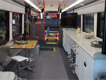 the air-conditioned bus includes a kids zone play area, seating, and countertops to accommodate iPad workstations for residents to take a short survey (in English and Spanish) and two wide-screen monitors for presentations.