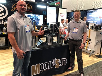 Jason Moore (left) and William Brahler stand alongside the Moore Safe bottle jack in the Gaither Tool booth at the 2019 SEMA Show. They are holding the components that can be easily swapped in order to safely lift a vehicle. Moore invented the innovation that bears his name.