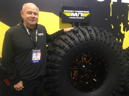 Todd Pickens, vice president of sales for Mickey Thompson Performance Tires & Wheels, stands next to a 58-inch version of the brand's recently announced Baja Pro XS light truck tire.