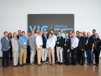 MCI and IMG members gather the Vehicle Innovation Center. From left are Ian Smart, MCI; Patricia Ziska, MCI; Gladys Gillis, The Starline Collection; Chuck Abbott, Gray Line Tennessee; Scott Riccio, Northeast Charter and Tour; Buddy Sload, Krapf Transportation; Brent Maitland, MCI; Dan Martin, Karst Stages; Mike Dixon, Southeastern Stages; Patrick Scully, MCI; Geoffrey Lynch, Hampton Jitney; Brian Parker, Southeastern Stages; Christian Holter, Rochester City Lines; Tom Skinner, Cline Tours; Dan Holter, Rochester City Lines; Frank Leyden, Cline Tours; Robert Lessor, MCI; Greg Gallup, Royal Coach T