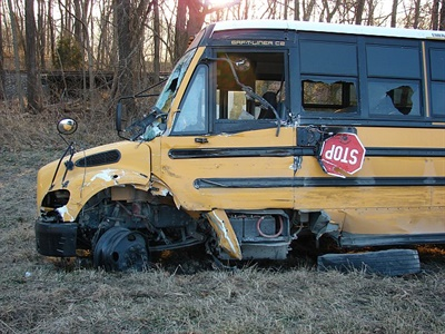 A semi tractor trailer in Indiana struck a school bus' front driver's side head on, skidded down the entire left side of the bus, and pushed the bus off the road. Photo courtesy Indiana State Police