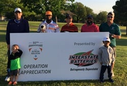 Golfers pose with sign at pro am event for military personnel.