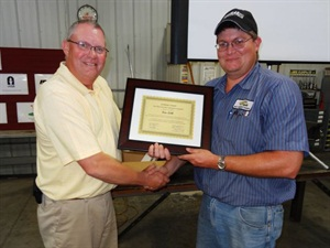 "Kevin Settle (right), winner of Iowa's ""Best of the Best"" competition for school bus technicians, accepts his award from Owen Freese, executive director of the Iowa Pupil Transportation Association."
