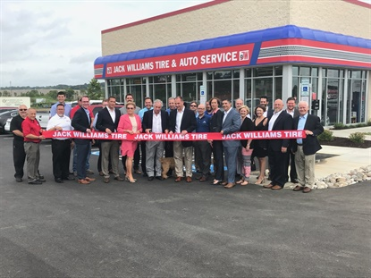 Bill Williams, center, gets ready to cut the ribbon on the company's 36th store. The company was founded in 1929.