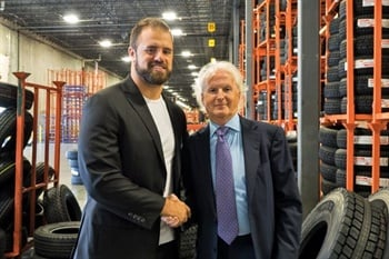 New England Patriots fullback James Develin (left) is pictured with Sullivan Tire Vice President Paul Sullivan at the company's warehouse in Taunton.