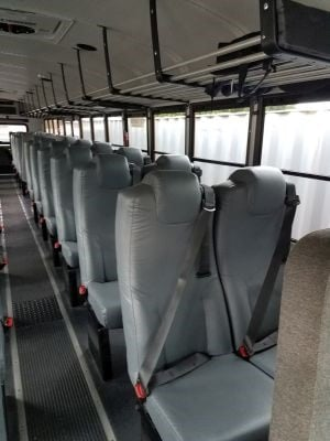 Upgrades on Jericho's bus include air-ride suspension, driver seat air ride, drop-down screens for DVDs or CDs, overhead racks, tinted windows, and school-approved passenger bucket seats with three-point belts.