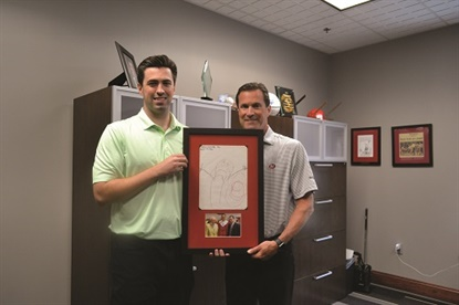 John McCarthy III and his father, John McCarthy Jr., pose with a drawing the younger McCarthy made before he entered kindergarten — a portrait of himself with a tire. Even then, he knew he wanted to join the family business. The drawing hangs in his father's office and is framed with a photo of them alongside John Jr.'s father, Jack McCarthy.