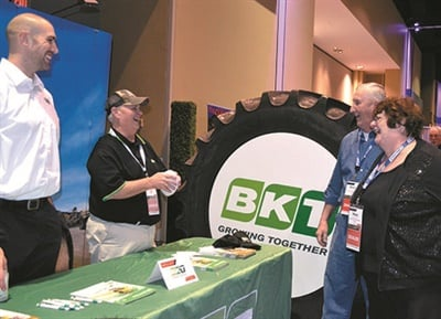 Bruce and Mary Faulkner talk about farm tires at the BKT booth with Loudan Hammersmith, left, and Dave Paulk, sales managers for the tire maker. Bruce Faulker manages the tire department and service center at Provision Partners Cooperative in Stratford, Wis., and he was among the 350 tire dealers to attend K&M's annual conference.