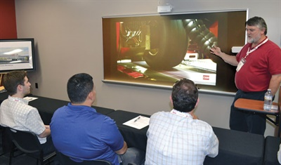 Sam Knisley, research specialist, instructs Jason Abood (Kenda, left), Luis Escoto (TGI, center) and Chris Wood (Tire Discounters Inc.) on the fine points of vehicle dynamics.