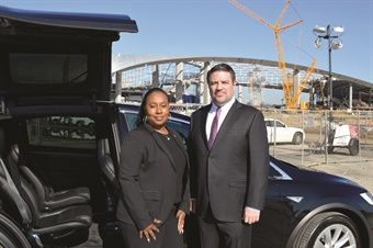 MOTEV chief administrative officer Tiffany Hinton and managing partner Robert Gaskill with a Tesla Model X at the construction site of the Los Angeles Rams Stadium in Inglewood, Calif. The company is involved with the Inglewood Chamber of Commerce, among other area community groups. (LCT photo by Kevin Haegele/art director)