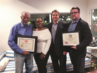 Actor Morgan Freeman (L) was presented MOTEV's 2019 LCT Operator of the Year Award in the 11-30 vehicles category on Dec. 6, 2019 in Malibu, Calif., by (L to R): Tiffany Hinton, chief administrative officer of MOTEV, LCT editor Martin Romjue, and MOTEV managing partner Robert Gaskill. Gaskill also showed Freeman the 2018 LCT People's Choice Innovation Award he received in November 2018 for his efforts with MOTEV. (LCT photo by Larry Johnson/MOTEV)