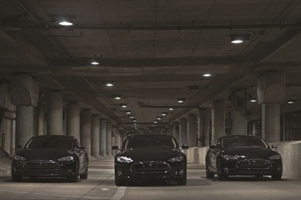 """Three of eMotion's six Tesla S sedans on Lower Wacker Drive in Chicago. The Teslas often work together as part of a """"Convoy"""" package, transporting up to 24 people at a time with high-precision driving and a special concierge car fitted with flashing lights to control traffic."""