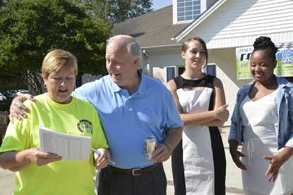 Dianne Benton reviews the schedule of events alongside Gary Faircloth, CEO and president of the Boys and Girls Homes of North Carolina, and two young women who rely on the charity. Black's Tire hosts an annual golf tournament to benefit the group.