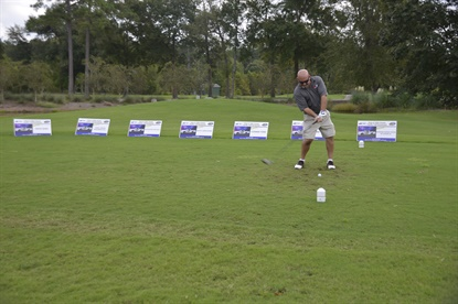 A golfer takes a swing against a backdrop of sponsorship signs during the charity golf tournament hosted by Black's Tire in 2015.