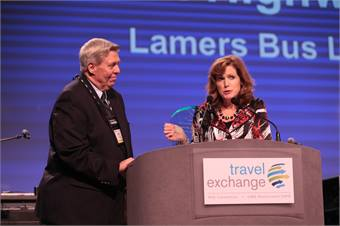 Allen Lamers, president of Lamers Bus Lines, accepts the United Motor Coach Association's Green Highway Award, sponsored by MCI, from Patricia Ziska, MCI VP, private sector sales.