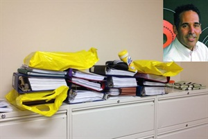 Peter Lawrence (inset) of Fairport (N.Y.) Central School District completed his doctorate last week. In the binders and yellow bags pictured here are the books he used in writing his dissertation.