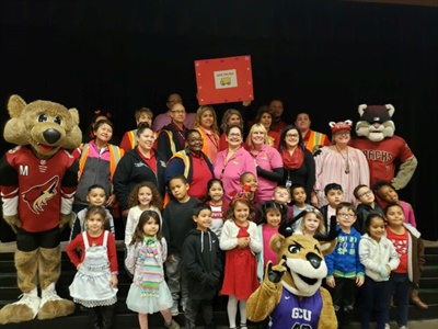 Mascots from Arizona sports teams joined the Love the Bus celebration at Glendale Elementary School District #40. Doris Bean, the manager of transportation for the district, is shown in the third row, far right.