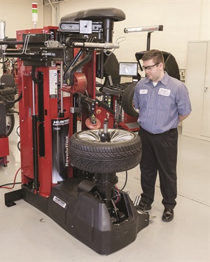 The automatic Hunter Revolution tire changer is mostly operated by pressing on a foot pedal, which safely distances the operator (Miles Dierker) from the assembly. Photo provided by Hunter Engineering.