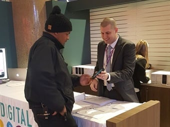 A Keolis representative training a conductor on how to use an iPhone programmed by Keolis. Photo courtesy of Keolis Commuter Services.