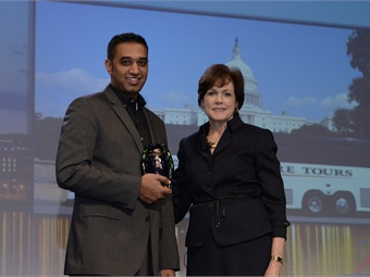 MCI VP, new coach sales, Patricia Ziska, right, presents the ABA Green Spirit Award to Adventure Tours President Adnan Khan.