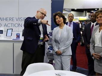 Clever Devices' Buddy Coleman talks tech to U.S. DOT Secretary Elaine Chao (center) along with U.S. FTA Acting Administrator Jane Williams (far right).