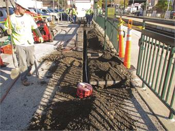 Construction workers install an electrical conduit needed for the new fare system at the Fox Chase Regional Rail Station in Philadelphia.